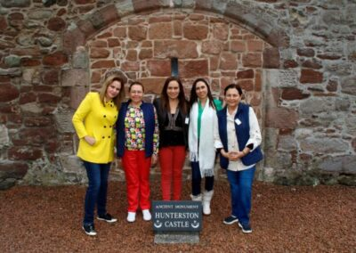 Hunterston Castle with five female visitors standing beside the Ancient Monument sign
